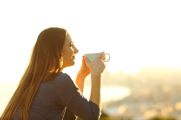 mujer contemplando la puesta de sol sosteniendo taza de café - café bebida fotografías e imágenes de stock