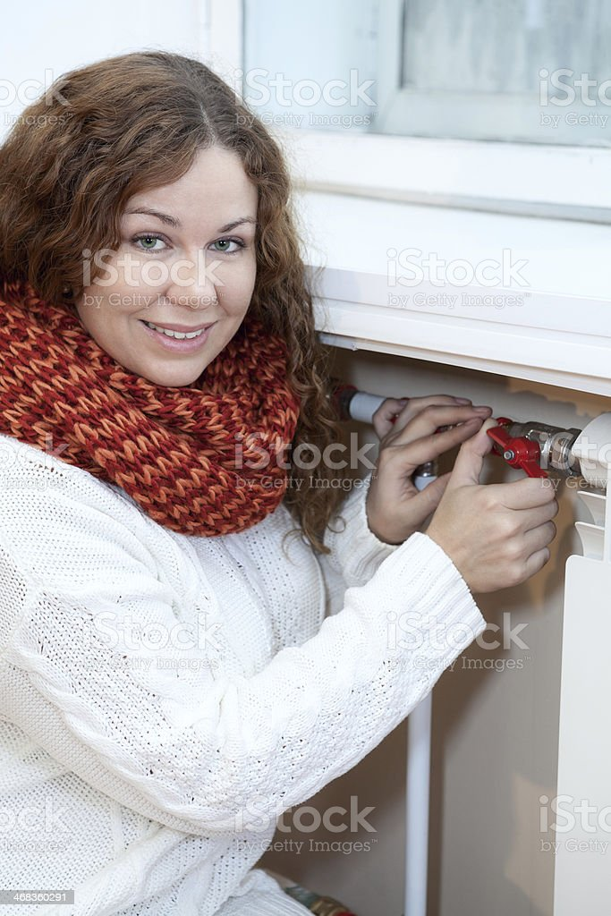 Woman controling the temperature of heating radiator in domestic room royalty-free stock photo