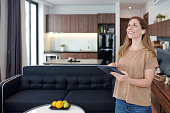 Joyful young woman with digital tablet using smart home app to control air conditioner temperature