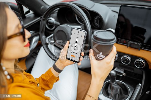 501071464 istock photo Woman controlling car with a smart phone 1205198958
