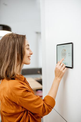 Frau Steuert Heizung Mit Einem Intelligenten Gerät Stockfoto und mehr Bilder von Ausrüstung und Geräte