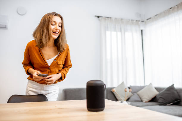 Woman controlling home devices with a voice commands stock photo