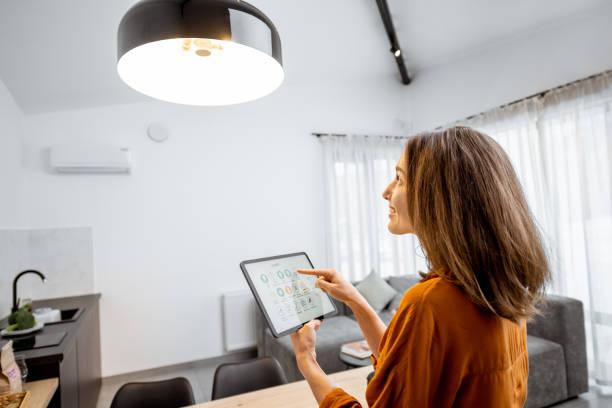 Vrouw die licht bestuurt met een digitale Tablet thuis foto