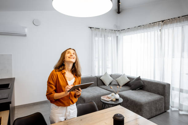 Woman controlling light with a digital tablet at home stock photo