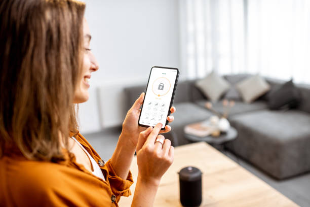 Woman controlling security from a mobile device stock photo