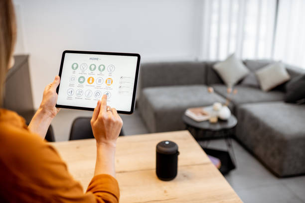 Woman controlling smart devices with a digital tablet at home stock photo