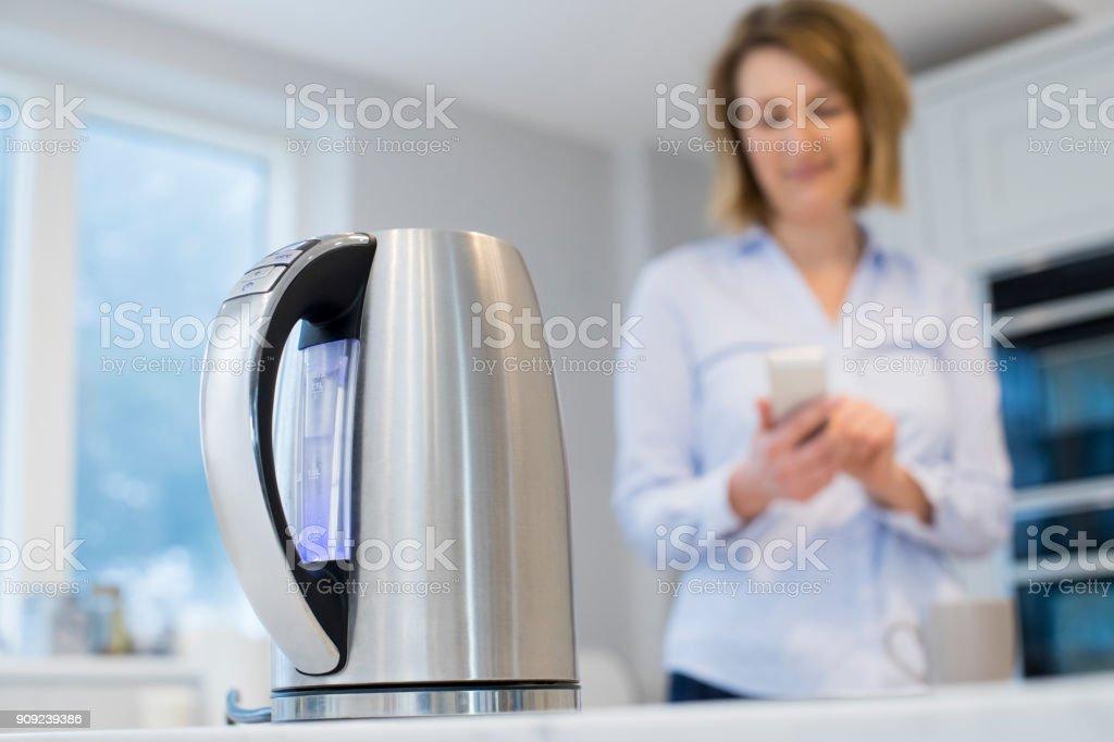 Controlar la caldera inteligente usando la aplicación móvil de la mujer foto de stock libre de derechos