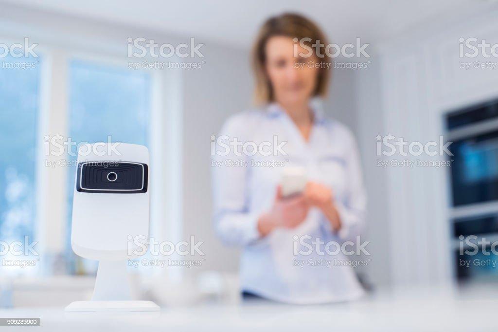 Frau Steuerung Smart Security Kamera mit App auf Handy – Foto