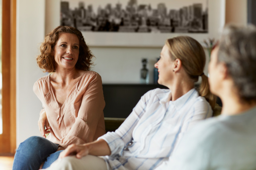 Happy mature woman conversing with female friends in living room at home