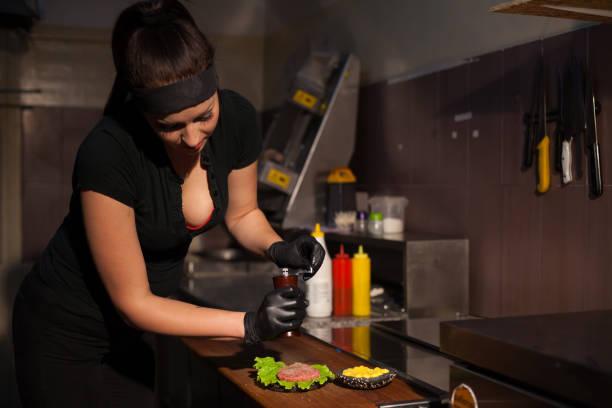 vrouw kok bereidt een hamburger in de keuken - hand constructing industry stockfoto's en -beelden