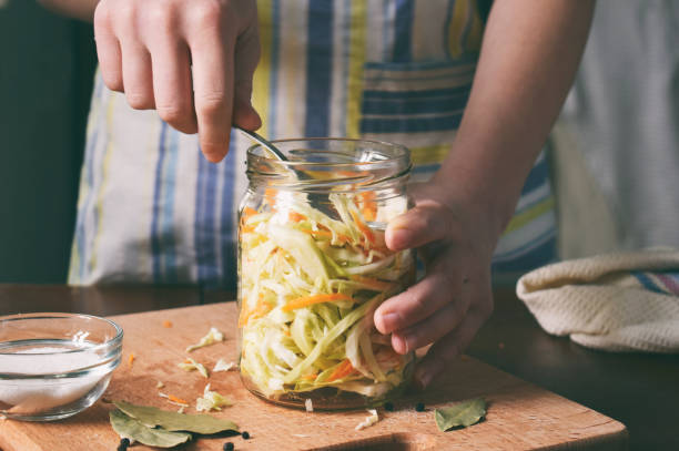Woman cook sauerkraut or salad on wooden background. Step 5 - Put the cabbage in the jars. Fermented preserved vegetables food concept. Woman cook sauerkraut or salad on wooden background. Step 5 - Put the cabbage in the jars. Fermented preserved vegetables food concept fermenting stock pictures, royalty-free photos & images