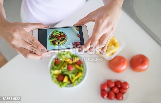 istock Woman cooking at home and taking a picture of her food 823631922