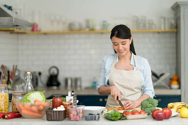 woman cooking at home - woman cooking stock pictures, royalty-free photos & images