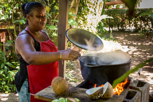 Woman cooking beans in Costa Rica Cahuita, Costa Rica - September 22, 2017: Woman in Costa Rica cooking beans (Caribbean typical food) in a big cooking pan with firewood. limoen stock pictures, royalty-free photos & images
