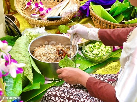 Thai Traditional Snack and Dessert, Woman Cooking Miang Kum or Sweet and Spicy Betel Leaf and Lotus Petal Wrap Filled with Coconut, Peanuts, Dried Shrimp, Chiles and Lime.