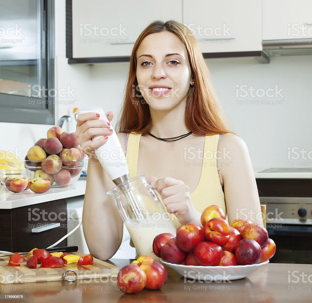 woman cooking dairy beverages with  nectarines at  kitchen royalty-free stock photo