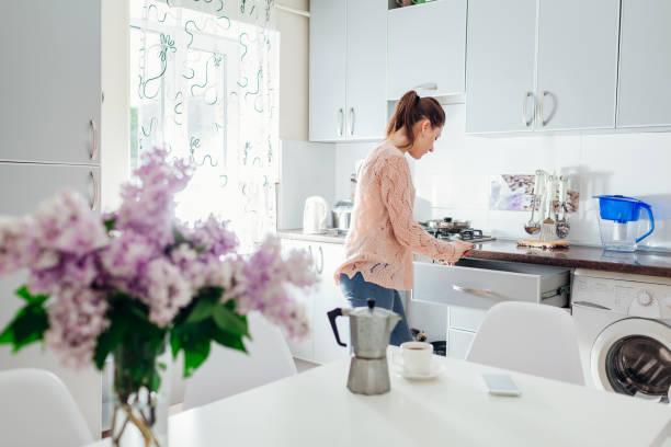 frau, kochen abendessen und kaffeetrinken auf dem küchentisch. moderne küchendesign. - silberzwiebeln stock-fotos und bilder