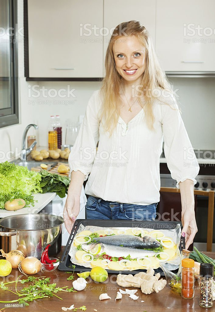 woman cooking  fish with potato in sheet pan stock photo