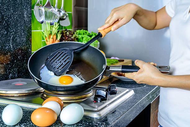 Woman cooking fried egg with kitchenware in kitchen/ lifestyle conceptual – zdjęcie