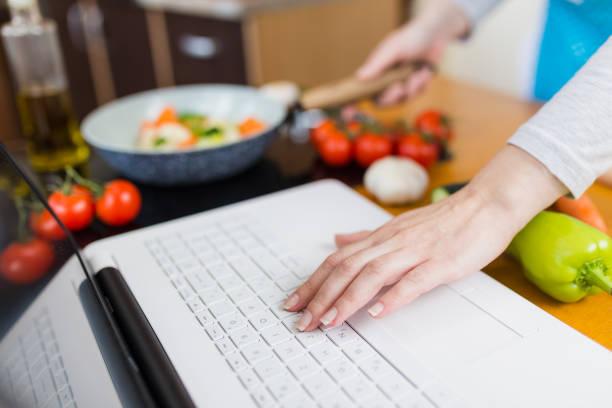 Mujer cocinando comida saludable. Concepto de blog de comida. Trabajo desde casa multitarea. - foto de stock