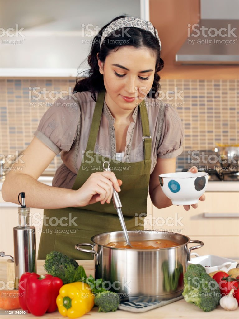 Woman cooking in domestic kitchen stock photo