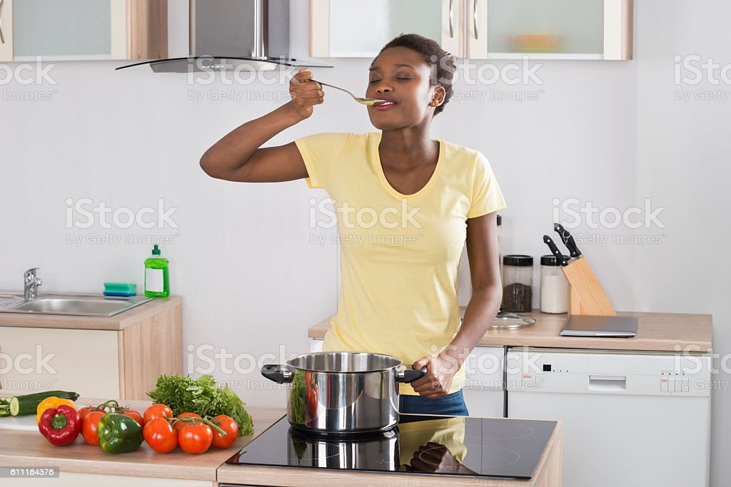 Woman Cooking Meal In Kitchen stock photo