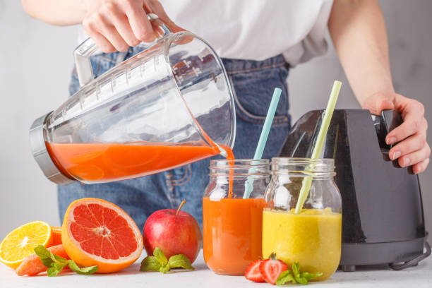 Woman cooking multicolored summer fruit juices or smoothie in glass jars and ingredients on white table. stock photo