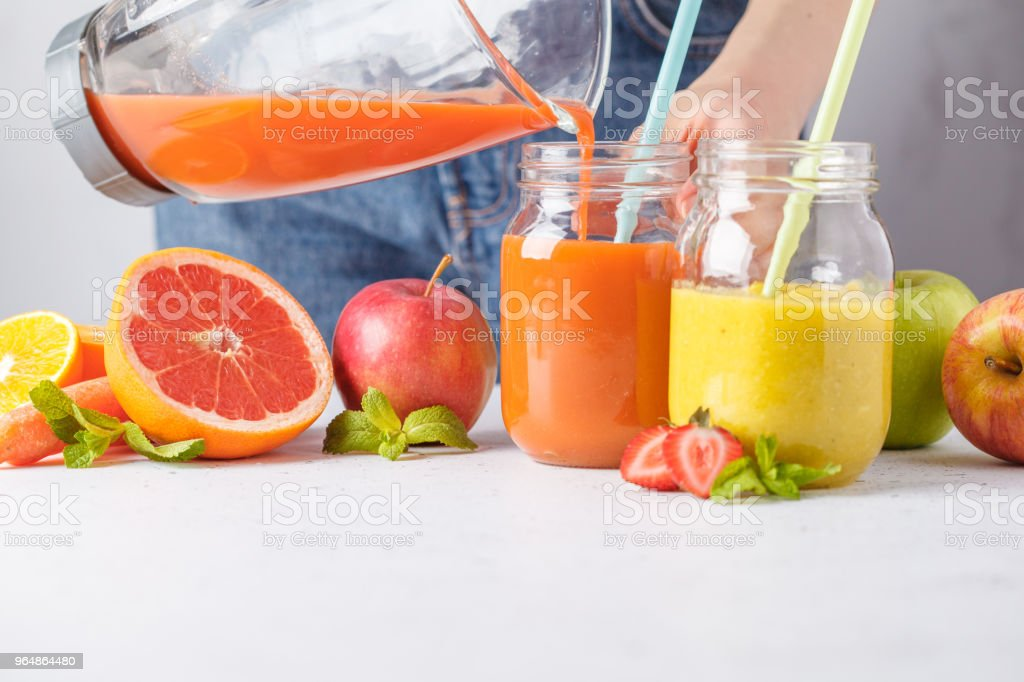 Woman cooking multicolored summer fruit juices or smoothie in glass jars and ingredients on white table. royalty-free stock photo
