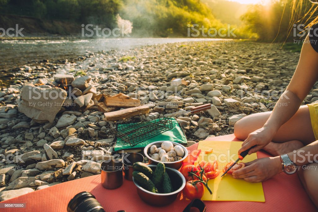 woman cooking on camp fire. wild nature resting. cutting tomatoes stock photo