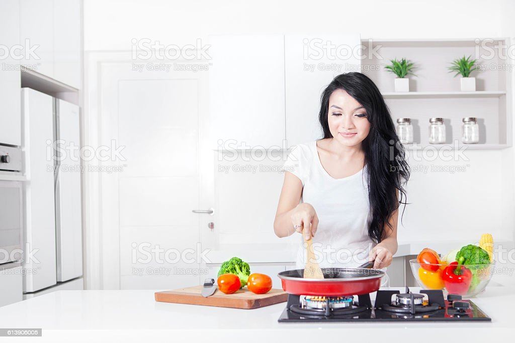 Woman cooking on the stove with frying stock photo
