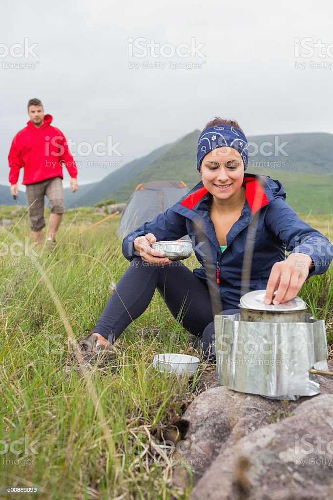 Woman cooking outside on camping trip with boyfriend walking stock photo