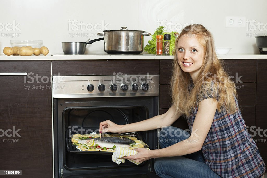woman cooking saltwater fish  in oven at  kitchen royalty-free stock photo