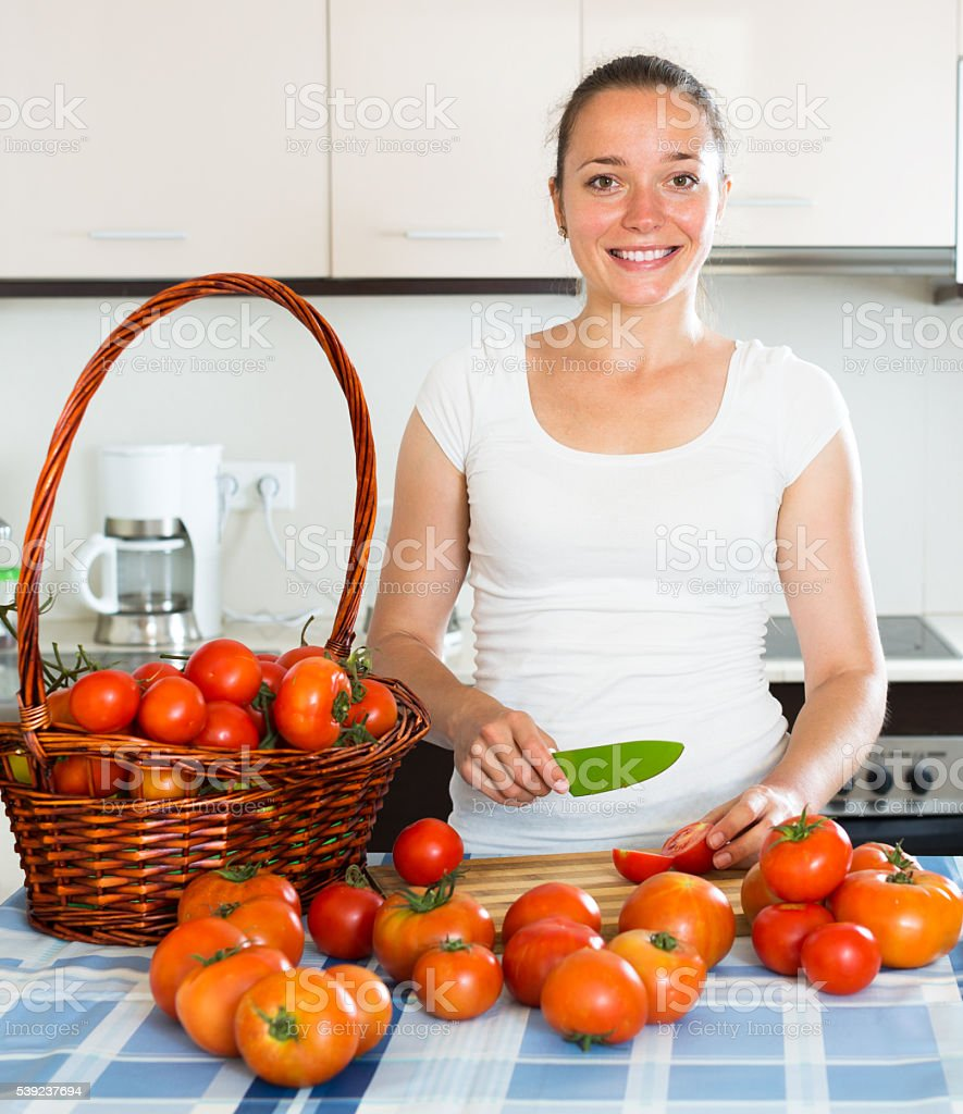 woman cooking tomatoes stock photo