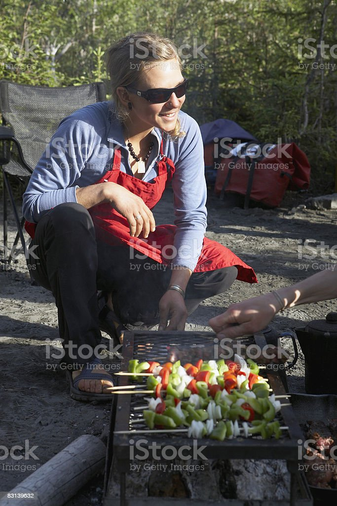 woman cooking vegetable kebabs on camp grill royalty free stockfoto