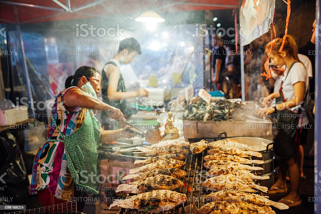 Woman cooks fish and seafood stock photo