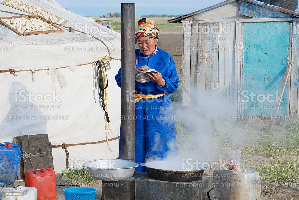 Woman cooks in front of the yurt in steppe, Mongolia. stock photo