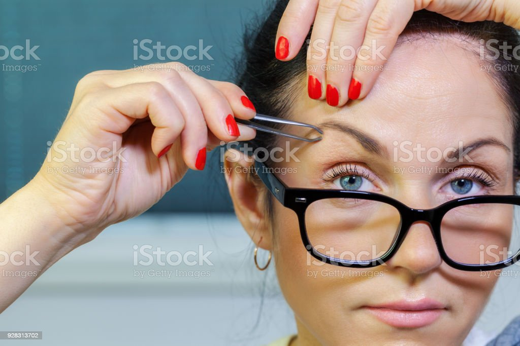 Woman correcting eyebrows stock photo