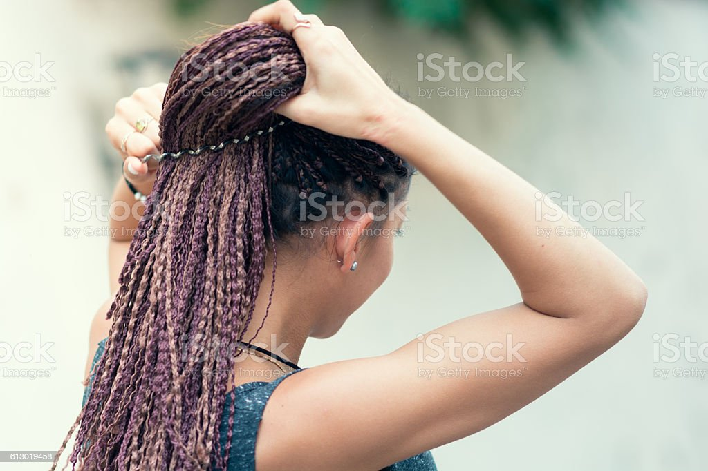 Woman correcting her hair cornrows at the street stock photo