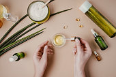 istock Woman cosmetologist cosmetics testing. Natural organic cosmetics. Serum hair mask. Flat lay pastel 1164263699