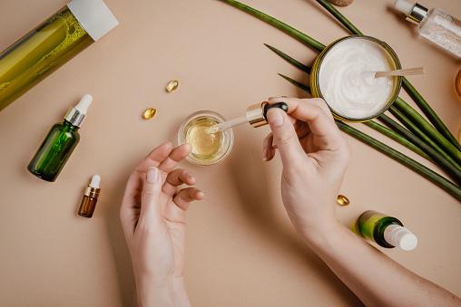 istock Woman cosmetologist cosmetics testing. Natural organic cosmetics. Serum hair mask. Flat lay pastel 1164264578