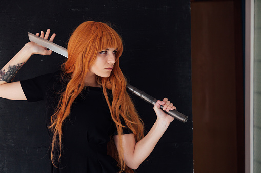 istock Woman cosplayer anime with red hair holds a Japanese sword 1212016382