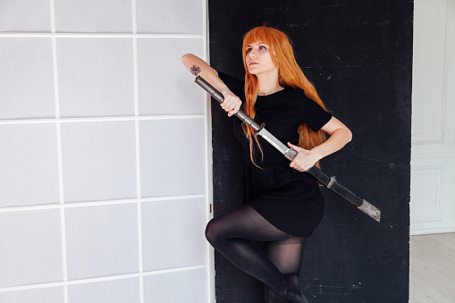 istock Woman cosplayer anime with red hair holds a Japanese sword 1212016441