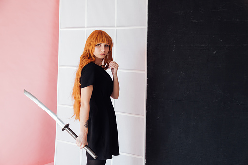 istock Woman cosplayer with red hair holds Japanese sword 1212016080