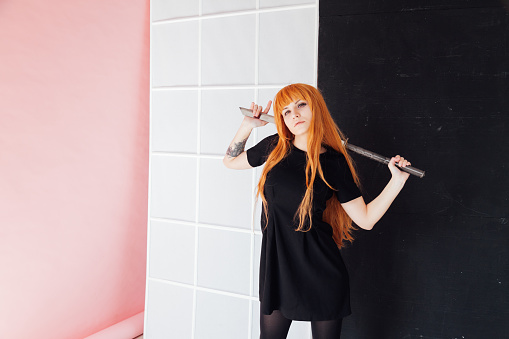 istock Woman cosplayer with red hair holds Japanese sword 1212016267