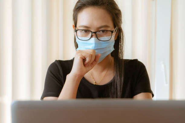 woman cough with face mask protection while working, Coronavirus, air pollution, allergy sick woman with medical mask stock photo