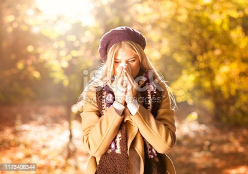 Woman coughing and blowing her nose in autumn. Cold and flu