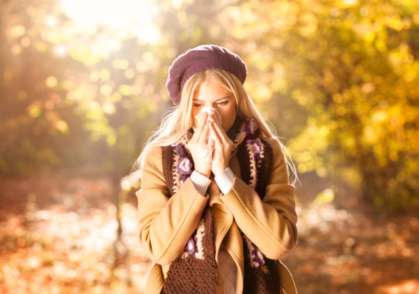 Woman coughing and blowing her nose in autumn Woman coughing and blowing her nose in autumn. Cold and flu allergy stock pictures, royalty-free photos & images