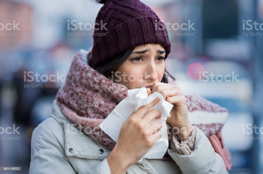 Woman coughing in winter stock photo