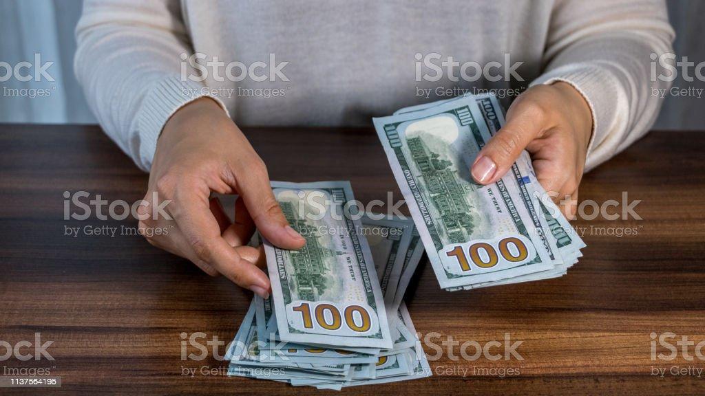 Mulher que conta dólares - foto de acervo