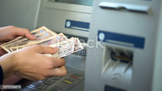 istock Woman counting Japanese Yen withdrawn from ATM, 24 hours service, easy banking 1072205074